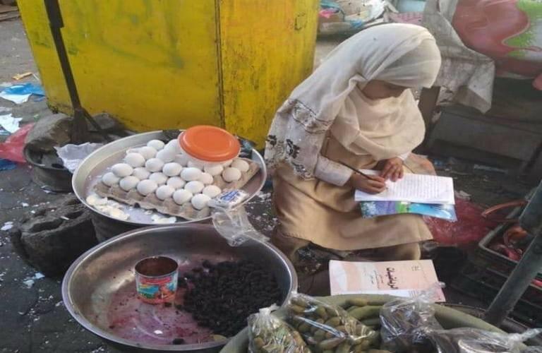 طفلة يمنية تعمل وتذاكر دروسها في إحدى الشوارع